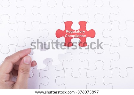 Hand embed missing a piece of puzzle into place, red space with word REGULATORY COMPLIANCE concept