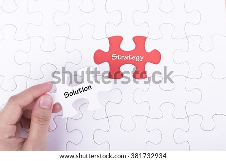 Hand embed missing a piece of puzzle into place, red space with word SOLUTION STRATEGY. Business and financial concept.