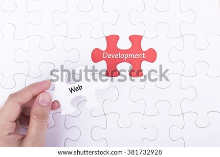 Hand embed missing a piece of puzzle into place, red space with word WEB DEVELOPMENT. Business and financial concept.