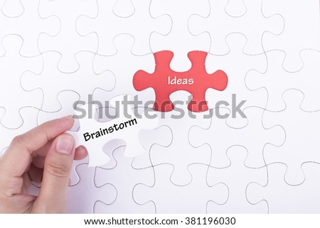 Hand embed missing a piece of puzzle into place with word BRAINSTORM IDEA, business and financial  concept.