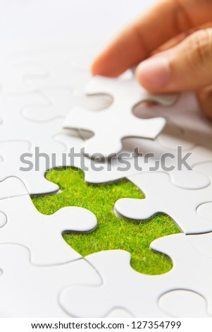 Hand embed missing puzzle piece into place, green space concept