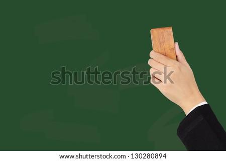 Hand erasing on chalkboard - stock photo