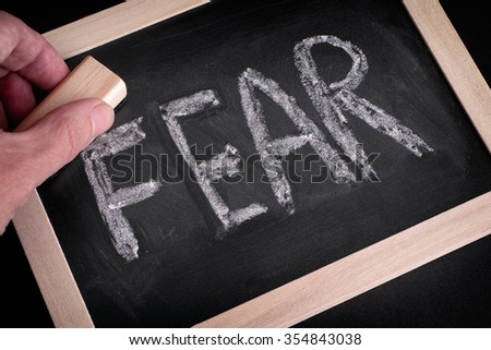 Hand erasing the word Fear on chalkboard. Close up. - stock photo