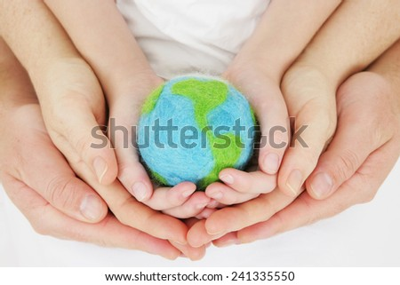 Hand felted world in generational hands - stock photo