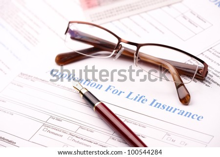 Hand filling in an application for life insurance with fountain pen - stock photo