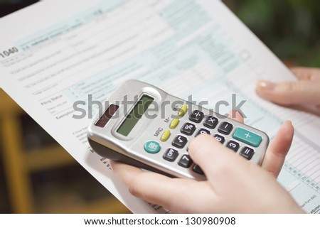 Hand filling income tax forms with calculator - stock photo