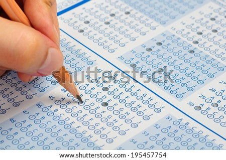 hand filling out answers to standard answer sheet - stock photo