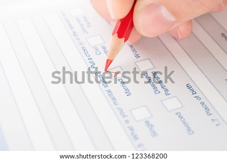 Hand fills questionnaire a red pencil - stock photo