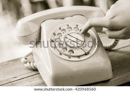 hand finger dialing number old day phone or rotary telephone on wood table vintage color tone - stock photo