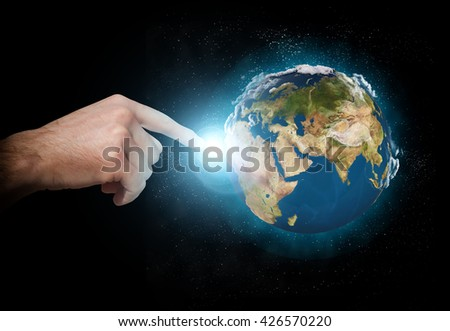 hand finger touches earth in space - stock photo
