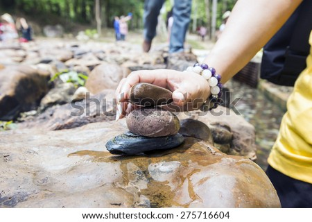 Hand finished stone tower. river background - stock photo