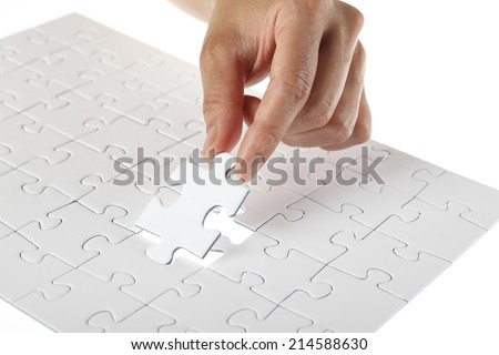 Hand finishing white puzzle - stock photo