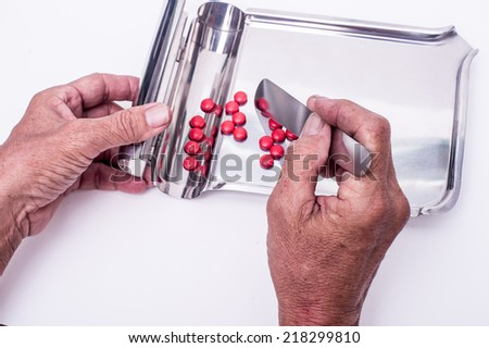 Hand fo counting pill on counting tray - stock photo