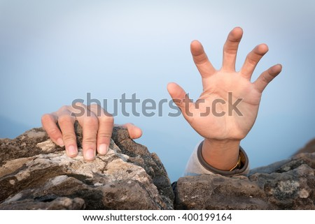 hand for help rock climbing - stock photo