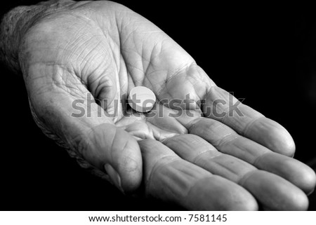 Hand from an old woman with a pill inside