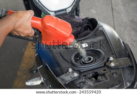 hand fuel nozzle in pouring to motorcycle at gas station - stock photo