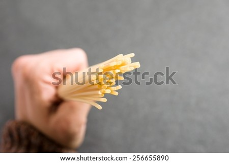 Hand full of raw dry spaghetti with grey background  - stock photo