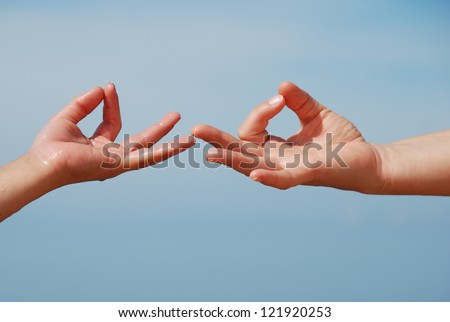 Hand gesture - Mudra - on the sky background, mother and child hand