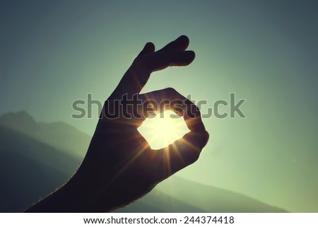 Hand gesture Ok with sun in the background - stock photo