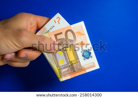 hand give money on a blue background - stock photo