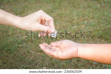 Hand gives coin to a boy - stock photo
