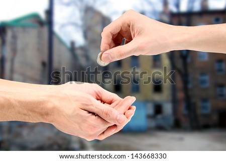 Hand gives coin to beggar on the street - stock photo