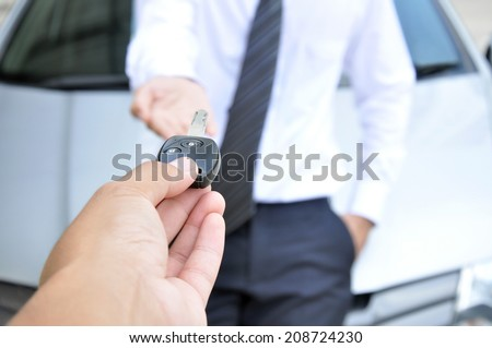 Hand giving a car key to another man - car sale & rental service concept