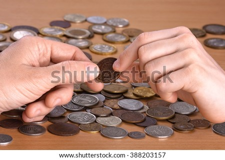 hand giving a coin to hand of another person