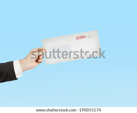 hand giving a envelope on blue background - stock photo