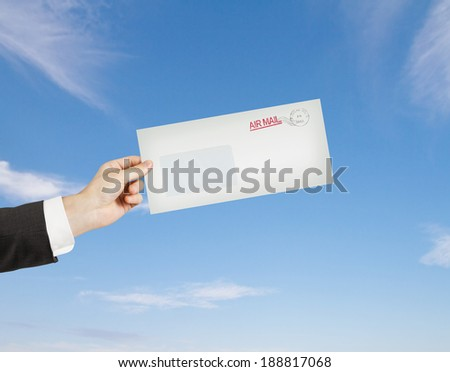 hand giving a envelope on sky background - stock photo