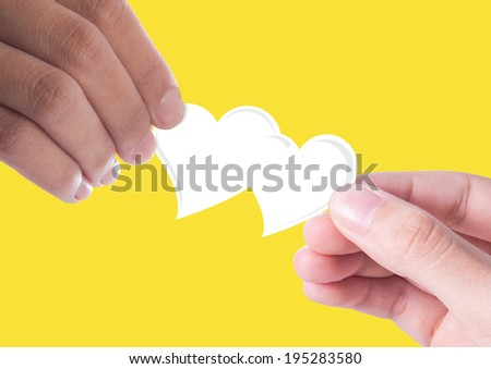 Hand giving a white heart to hand - stock photo