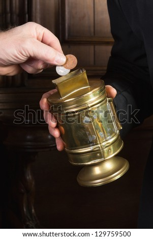 Hand giving coins to a priest collecting in church - stock photo