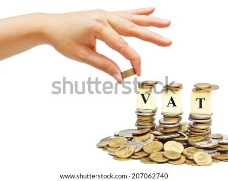 hand giving coins to piles of coins with the word VAT (Value Added Tax)  - stock photo