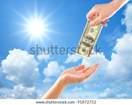Hand giving money to other hand over clouds and sun - stock photo