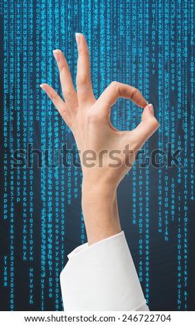 hand giving ok sign on matrix background - stock photo