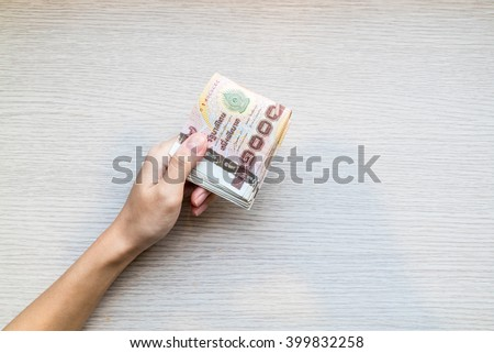 Hand giving stack of thousand bath Thai money with copy space - stock photo