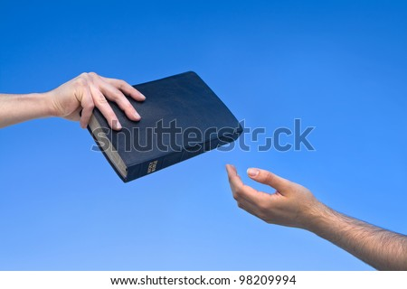 Hand giving the Bible to another person - stock photo