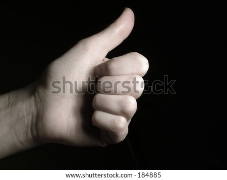 Hand giving thumbs up isolated on a black background