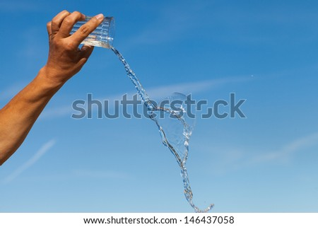 Hand, glass and water against blue sky.