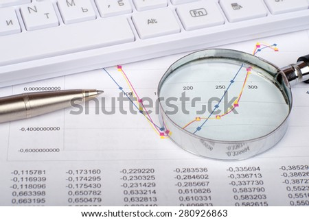 Hand glass with handle on document with numbers and graphs