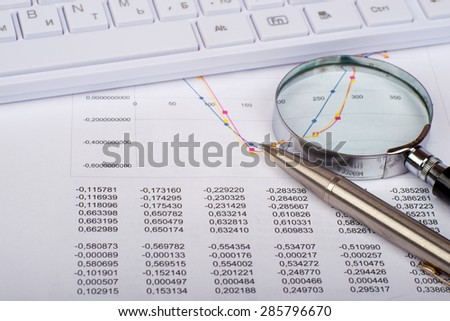 Hand glass with handle on document with numbers and white keyboard