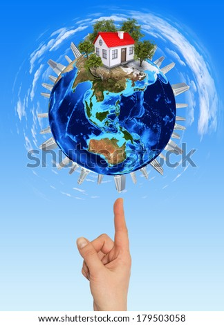 Hand goes to the planet Earth. Blue sky on background - stock photo