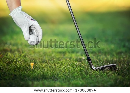 Hand golfers as gives the ground a golf ball on the tees - stock photo