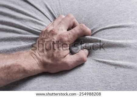 hand grasping sheets - stock photo
