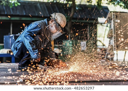 Hand grinding on steel plate by worker in factory.