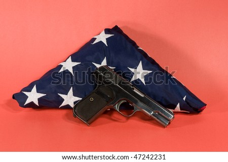 hand gun laying on  a folded american flag with a red background