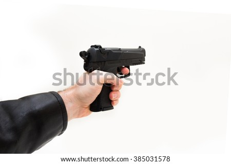 Hand gun taking aim from the side close up - stock photo