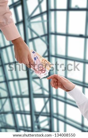 Hand handing over money to another hand - stock photo
