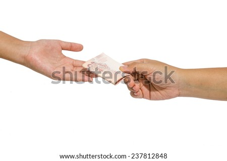 Hand handing over money to another hand - stock photo