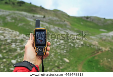 Hand held GPS being used for navigation in the mountains during rainy weather.